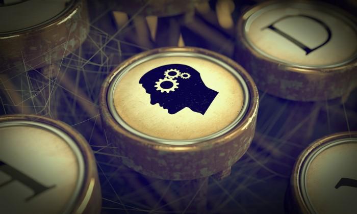 Head With Gears on Grunge Typewriter Key.